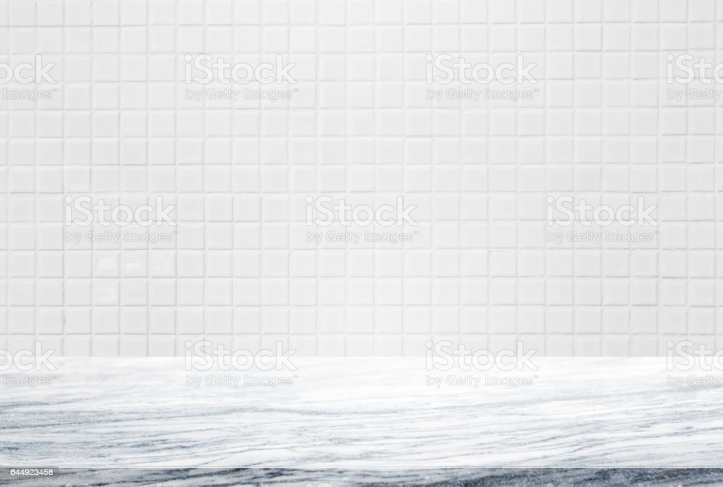 Stone table top and background of white ceramic tile wall