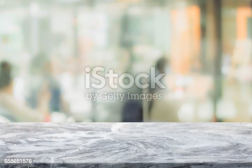 662984906istockphoto Stone table top and blurred restaurant interior background - can used for display or montage your products. 655651576