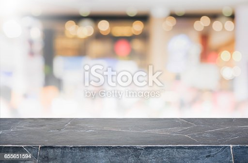 662984906istockphoto Stone table top and blurred restaurant interior background - can used for display or montage your products. 655651594