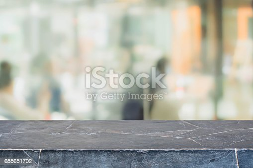 662984906istockphoto Stone table top and blurred restaurant interior background - can used for display or montage your products. 655651702
