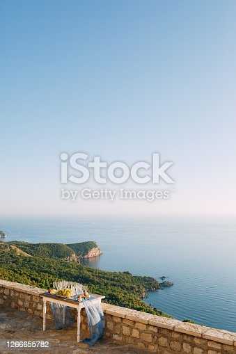 A stone table with a blue cape, champagne glasses and grapes overlooking the green forest and the water. High quality photo