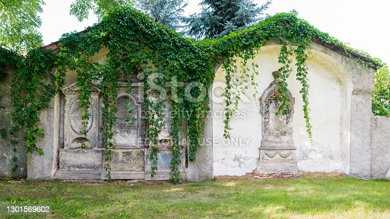 Mirsk, Poland - August 25, 2020; Stone tomb stele - a vertically positioned plate with an inscription or a relief stone decoration, also a vertical tombstone - placed on the fence of the church and cemetery