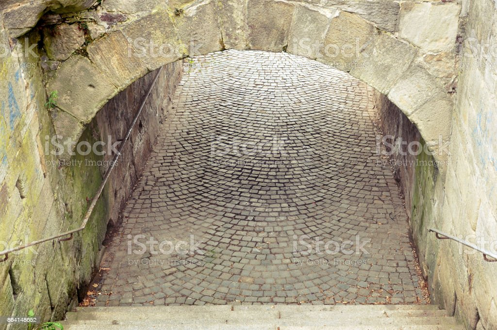 Stone tunnel under an ancient bridge. royalty-free stock photo