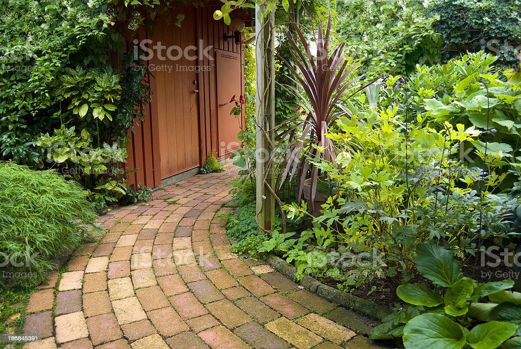 Stone walkway winding its way through the garden royalty-free stock photo