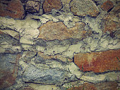 Close-up shot of an old stone wall with a lots of cement between stones.