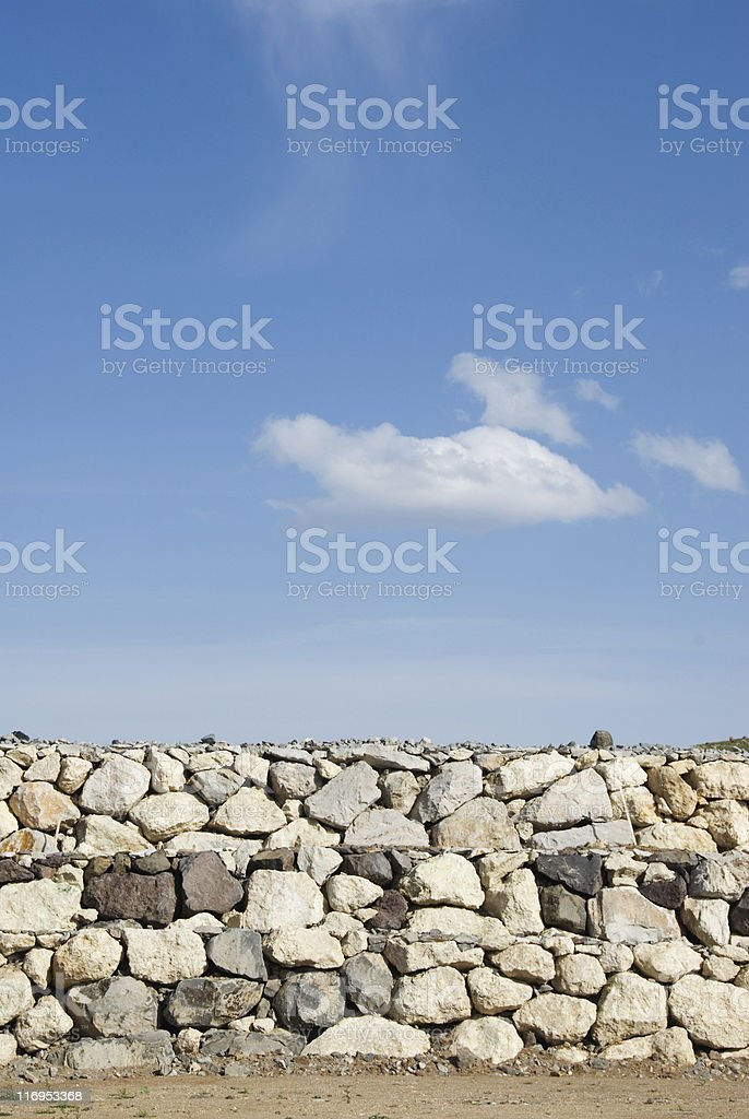 Stone wall against a blue sky royalty-free stock photo