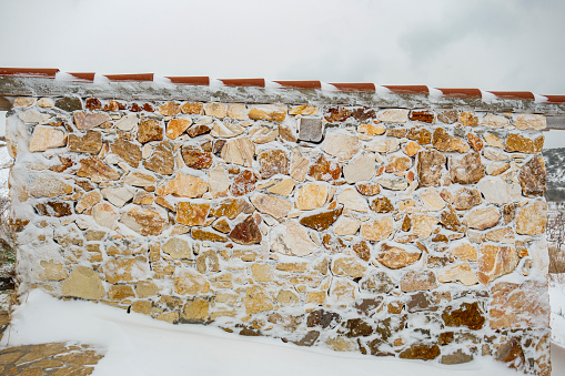Stone wall covered with fresh snow