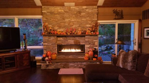 Stone Wall Fireplace Decorated in the Fall/Autumn Themes, Lit at Dusk stock photo