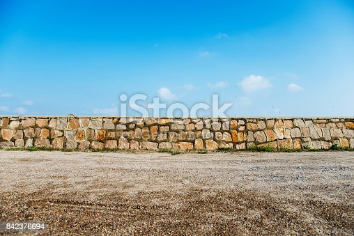 Stone wall in front of blue sky.