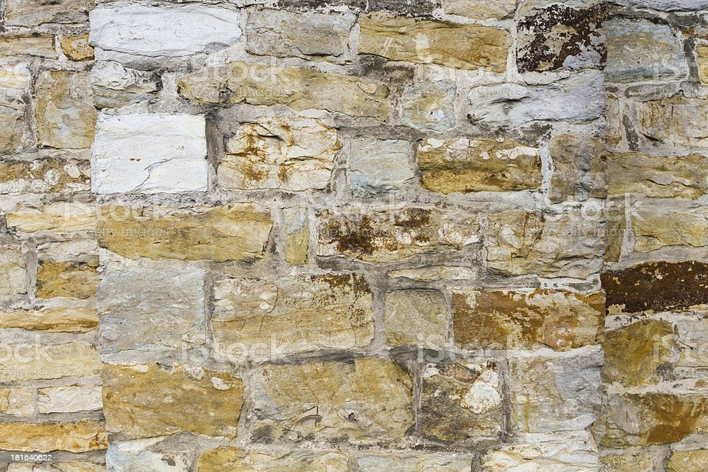 Stone wall outside with yellow stones and cement royalty-free stock photo