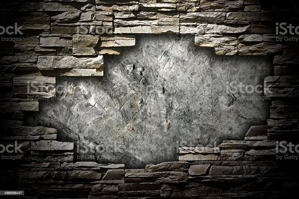 stone wall with a large hole in the middle stock photo