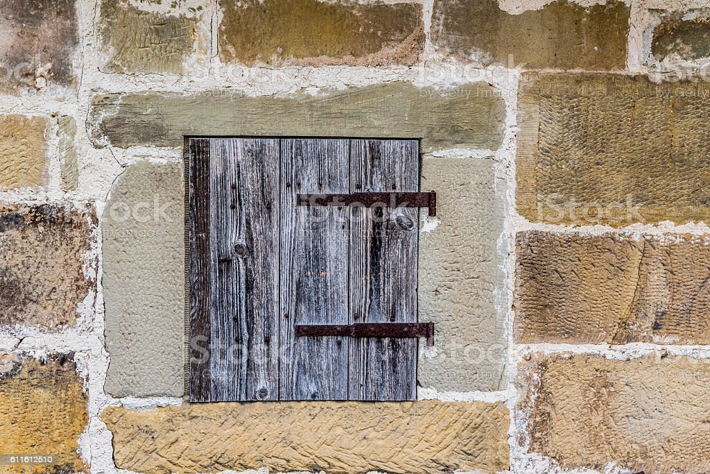 Stone wall with a wooden trapdoor stock photo