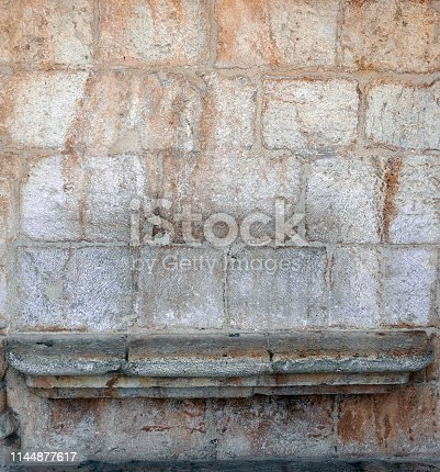A stone wall with a built in stone bench.