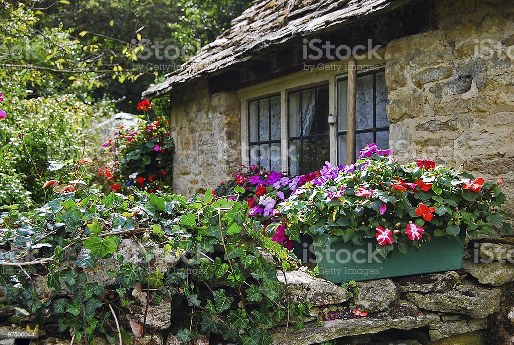 Stone wall with flowers of rural cottage in England royalty-free stock photo