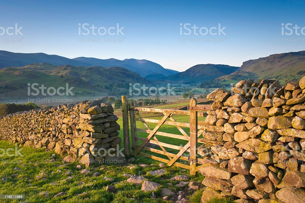 Stone wall with gate overlooking mountains and green fields stock photo