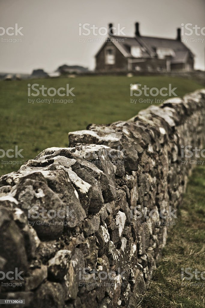 Stone Wall with Large House in the Background royalty-free stock photo