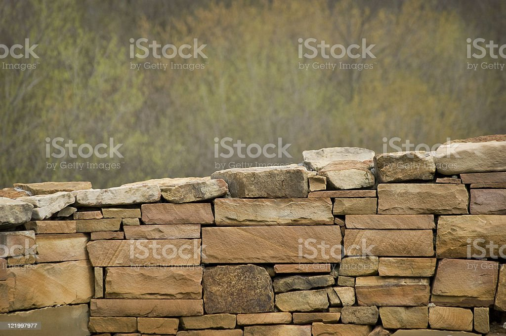 Stone Wall With OOF Trees In Background royalty-free stock photo