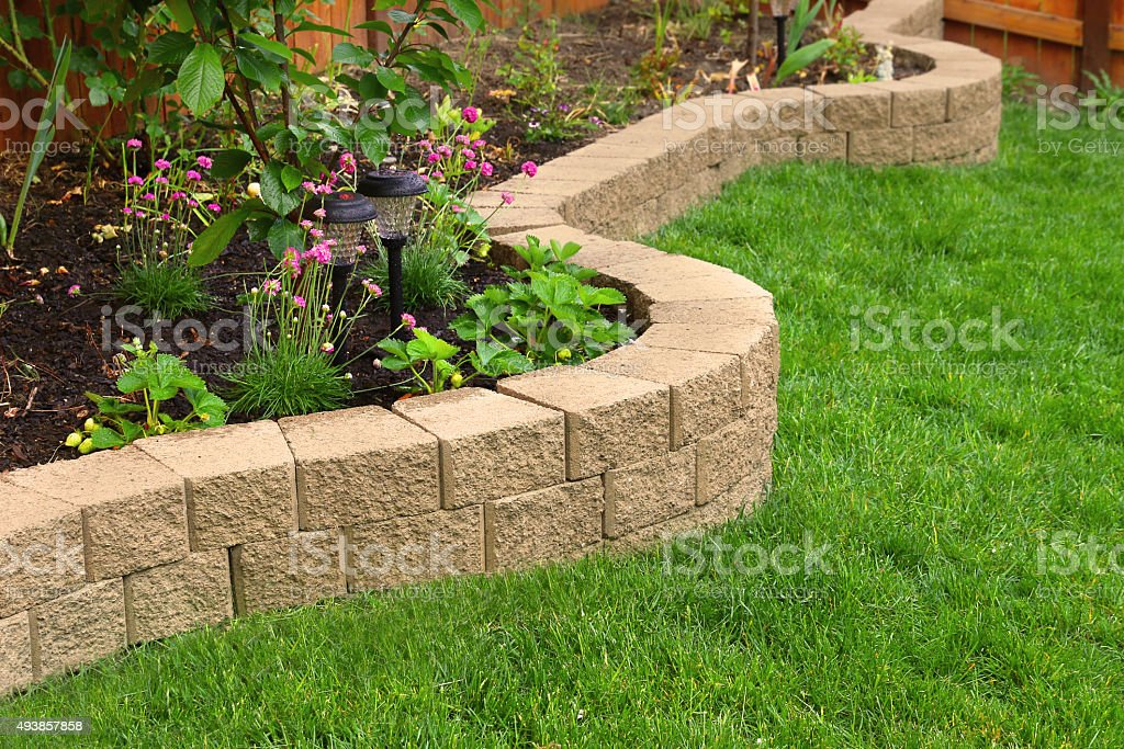 stone wall with perfect grass landscaping in garden with artificial grass stock photo