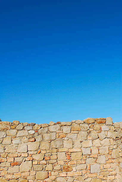 stone wall with vibrant blue sky stock photo