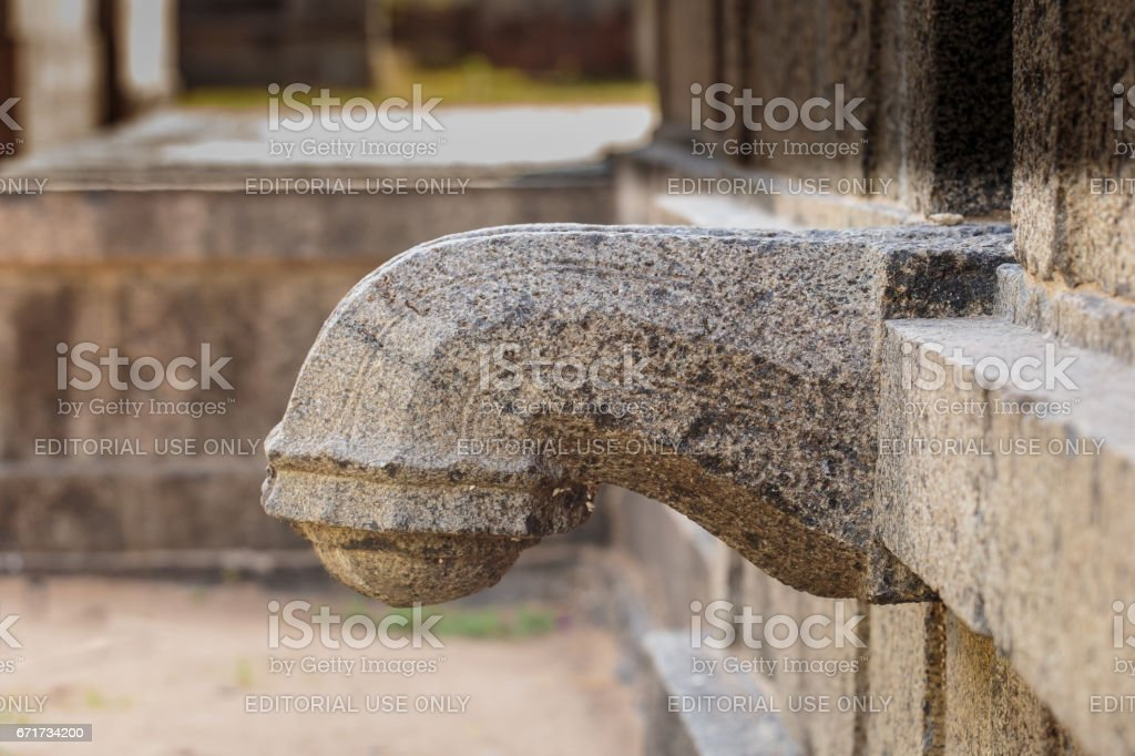 Stone water spout (gargoyle) in old Hindu temple, South India stock photo