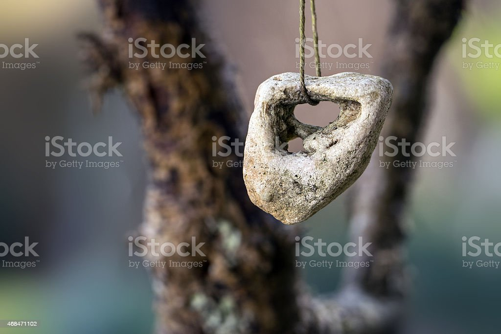 stone with a hole, adder stone against  blurred background with stock photo