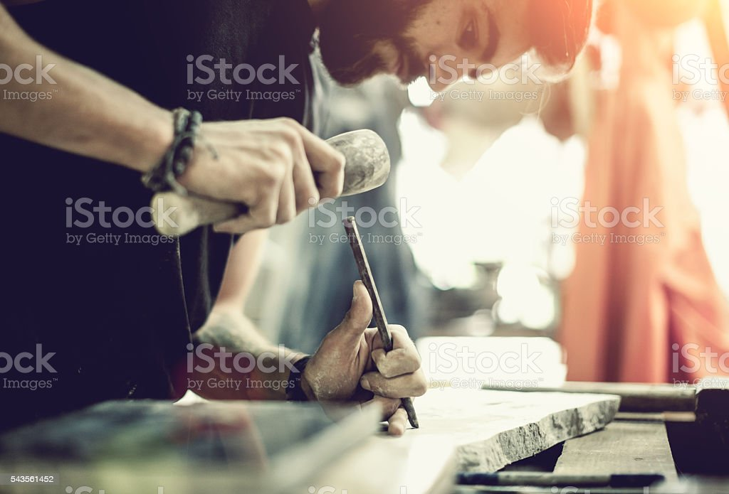 Stonecutter's hands in action stock photo