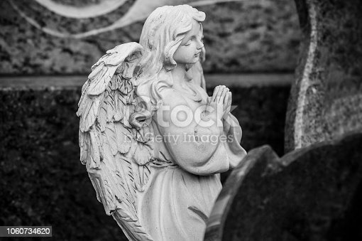 istock stoned angel praying on tomb at cemetery 1060734620