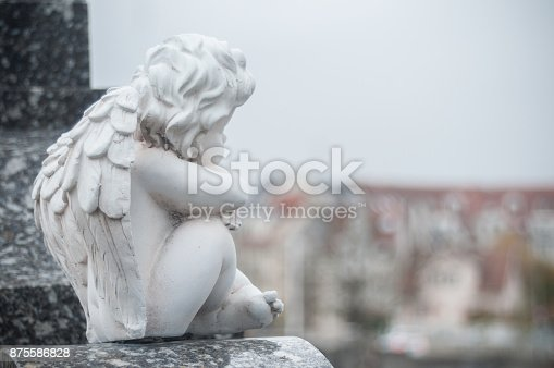 istock stoned angel sitting on tomb in a cemetery 875586828