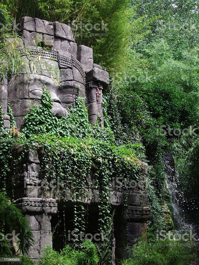 Stone-faced statue in the jungle surrounded by trees stock photo