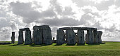 Close up of Stonehenge sunlit with dramatic clouds gathering