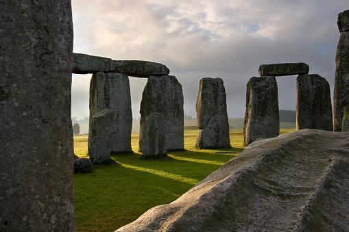 The sun rises, shedding it's rays through the massive hand carved stones at Stonehenge built on the Salisbury plains thousands of years ago.