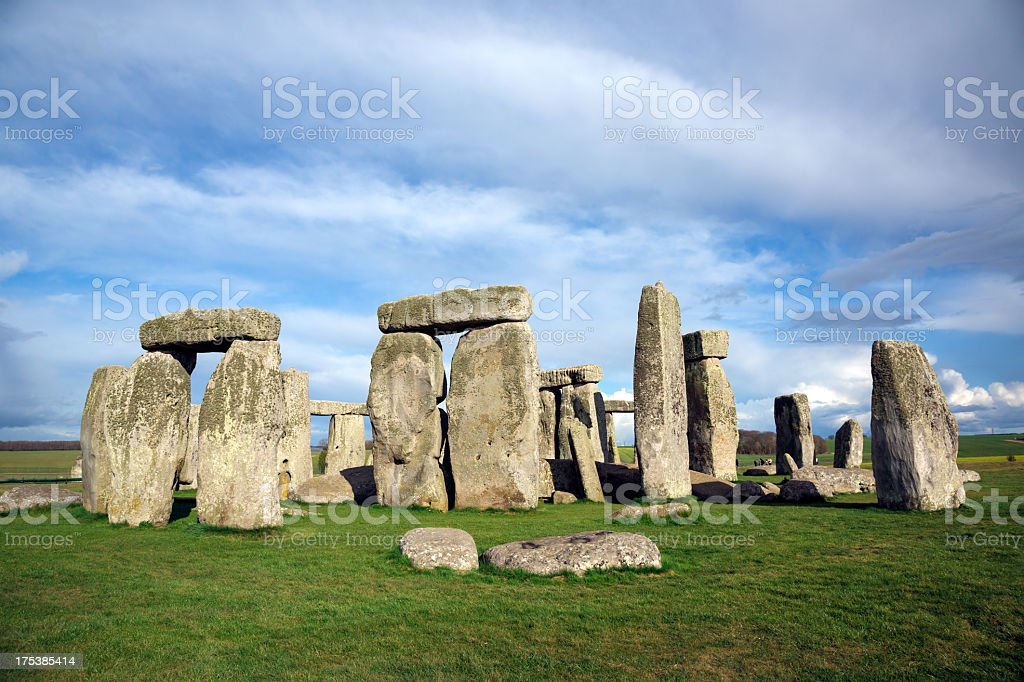 Stonehenge, Salisbury Plain, Wiltshire, England DSLR picture of the prehistoric monument of Stonehenge located in Wiltshire in England. The ring of standing stones is surrounded by green grass with a cloudy sky but sunny day of spring. Ancient Stock Photo