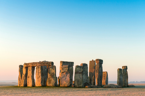 A wide angle view of Stonehenge in the landscape of Salisbury Plain, with the first light on a cold frosty morning.