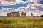 Salisbury Plain, UK - April 18 2014: View of Stonegenge, the famous prehistoric stone monument near Salisbury, England. Archaeologists believe that Stonehenge was constructed from 3000 to 2000 BC and it is an Unesco World Heritage Site. Stonehenge and Avebury, in Wiltshire, are among the most famous groups of megaliths in the world. The two sanctuaries consist of circles of menhirs arranged in a pattern whose astronomical significance is still being explored. These holy places and the nearby Neolithic sites are an incomparable testimony to prehistoric times.