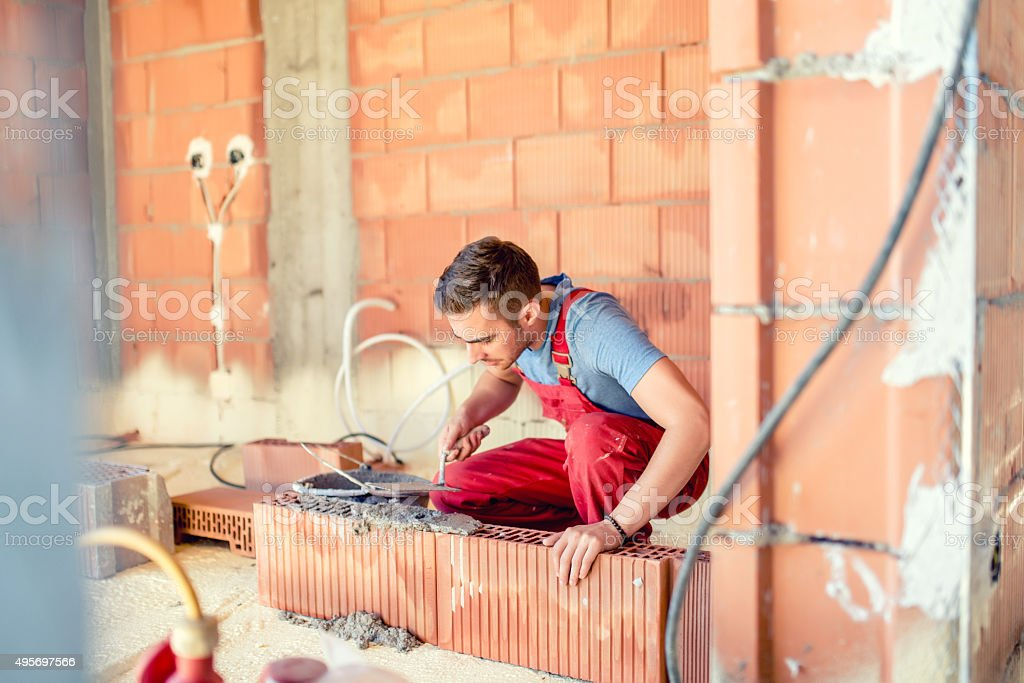 stonemason building walls, construction engineer and worker on site stock photo