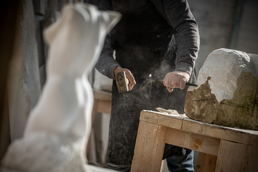 Close-up photo of a stonemason using a hammer and chisel to shape a piece of stone.