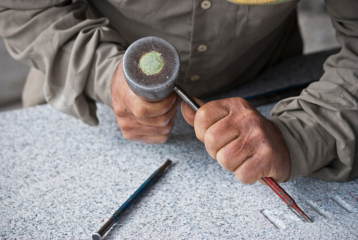 stonemason doing some letters on a granite stone