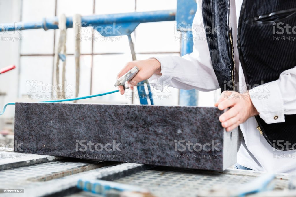 Stonemason working with compressed air at gravestone stock photo