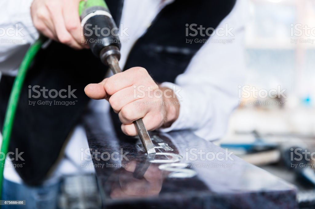 Stonemason working with pneumatic chisel stock photo