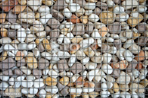Stones and pebbles wall in wire mesh