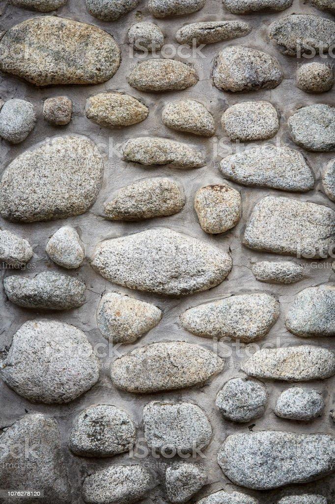 Stenen van achtergrond, grote grijze stenen, keien in het metselwerk, onderdeel van stenen omheining foto