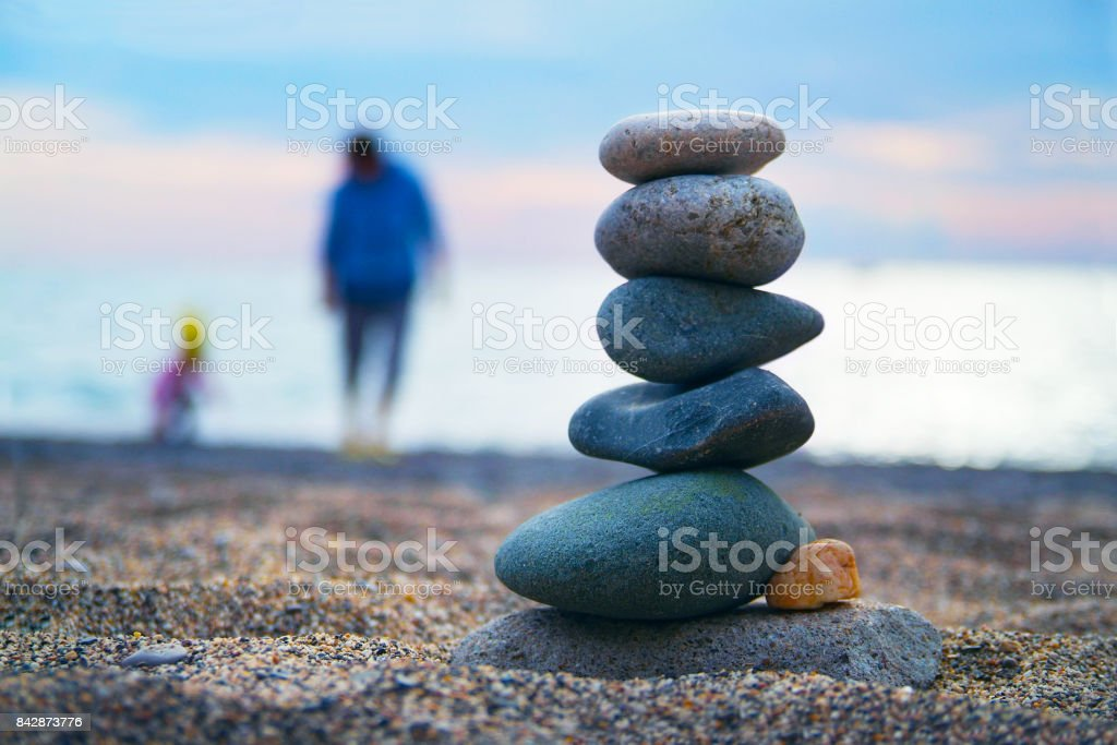 Stones balance and wellness spa concept. Close-up of pebbles stack over blue sea with non recognizable blurred parent and child at background stock photo