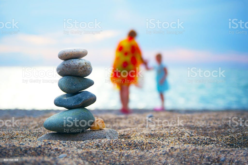 Stones balance and wellness spa concept. Close-up of pyramid of stones stack over blue sea with non recognizable blurred parent and child at background stock photo