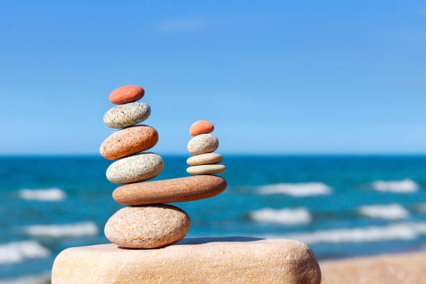 Stones balance on a background of blue sky and sea stock photo