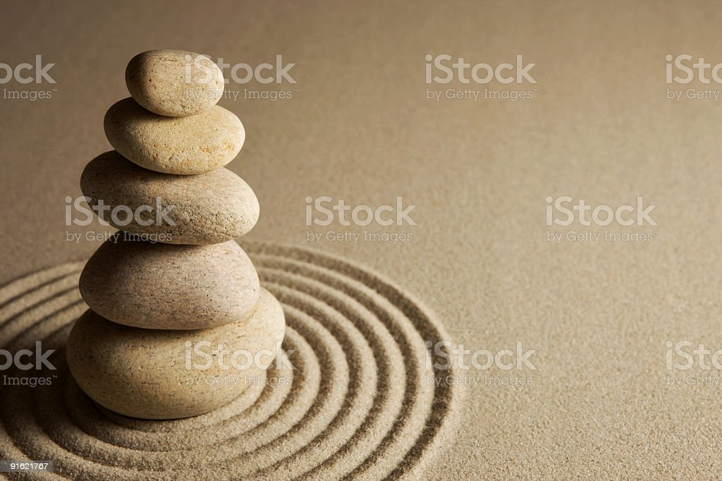 Stones balancing on sand in the center of a radial section royalty-free stock photo