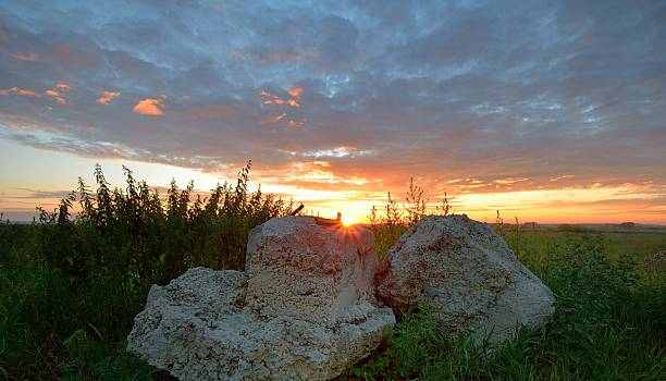 Cтоковое фото Stones in meadow on background of sunrise