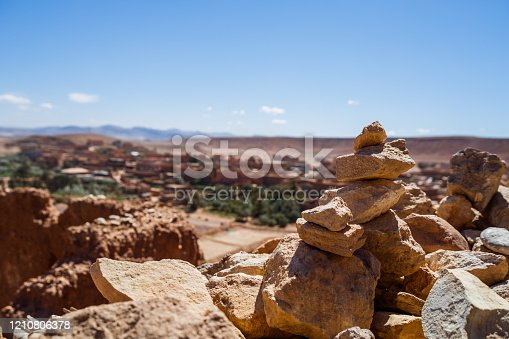 Image of stones in Morocco with village and desert behind.Focus on stones.