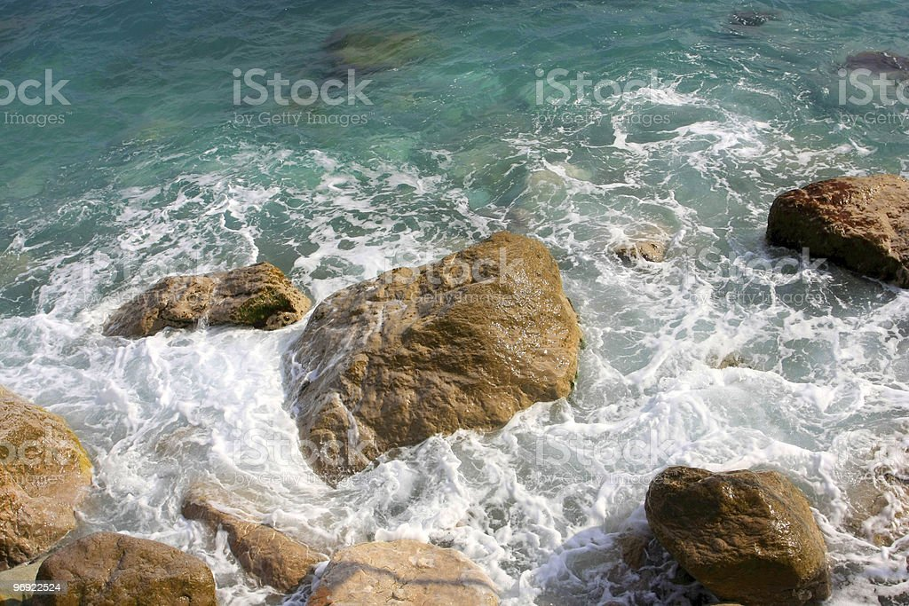 Stones in sea water and foam royalty-free stock photo