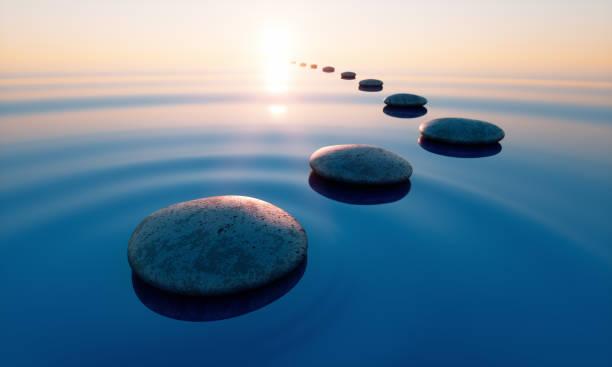 Stones in the ocean at sunrise stock photo