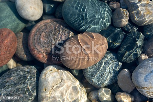 Ripples on the water surface in shallow water with colourful stones.